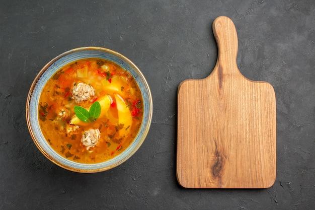 Widok z góry smaczna zupa jarzynowa z mięsem i ziemniakami na ciemnym danie stołowym posiłek mięsny