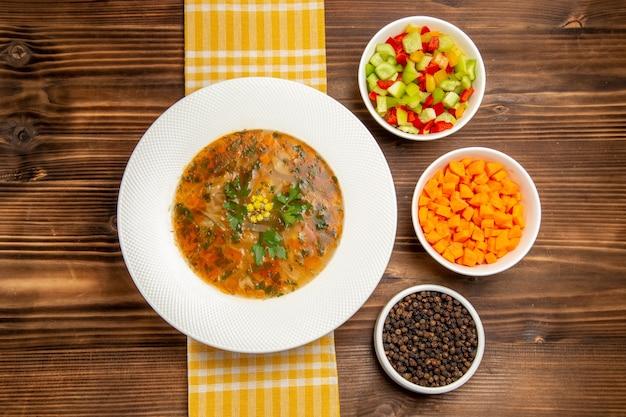 Widok z góry smaczna zupa jarzynowa z pokrojonymi warzywami na brązowym drewnianym biurku zupa jedzenie przyprawy warzywne