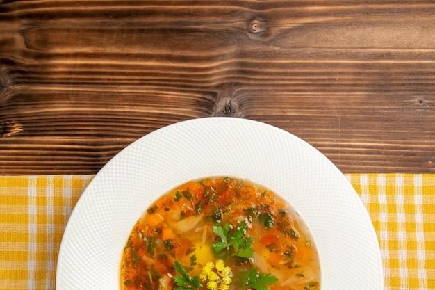 Widok z góry smaczna zupa jarzynowa z zieleniną na brązowym drewnianym stole zupa jedzenie przyprawa warzywna