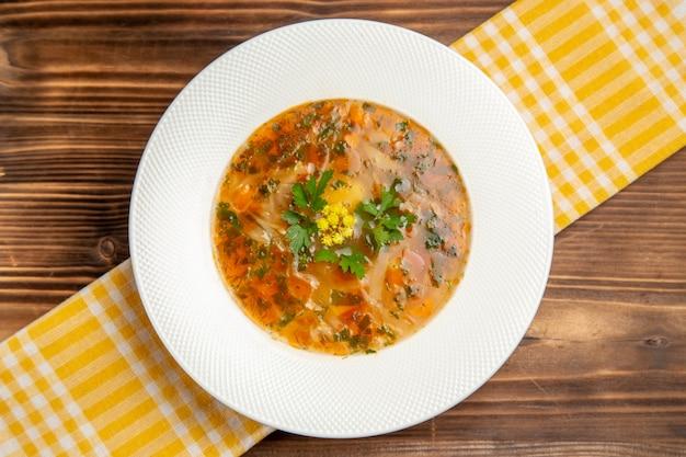 Widok z góry smaczna zupa jarzynowa z zieleniną na brązowym drewnianym stole zupa jedzenie przyprawy warzywne