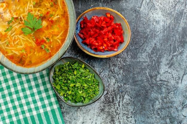 Widok z góry smaczna zupa makaronowa z zieleniną na jasnoszarym stole