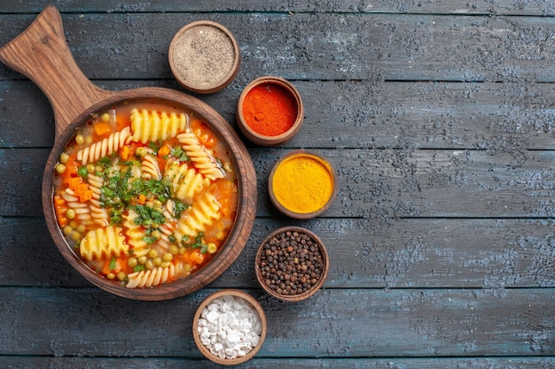 Widok z góry smaczna zupa makaronowa ze spiralnego włoskiego makaronu z różnymi przyprawami na ciemnym biurku kolor zupy włoskie danie kuchni makaronowej