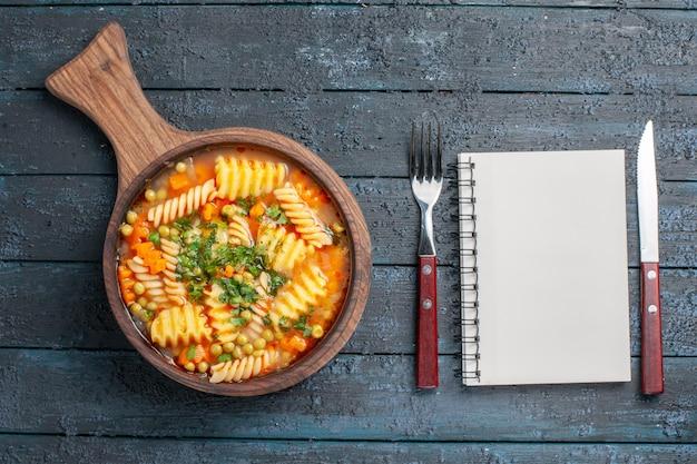 Widok z góry smaczna zupa makaronowa ze spiralnego włoskiego makaronu z zielenią na ciemnoniebieskim biurku danie zupy kolor włoska kuchnia makaronowa