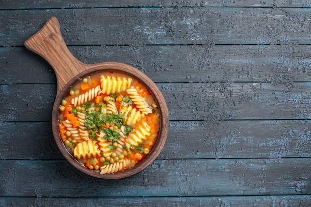 Widok z góry smaczna zupa makaronowa ze spiralnego włoskiego makaronu z zielenią na ciemnoniebieskim biurku zupa kuchnia warzywna danie kolor włoski makaron