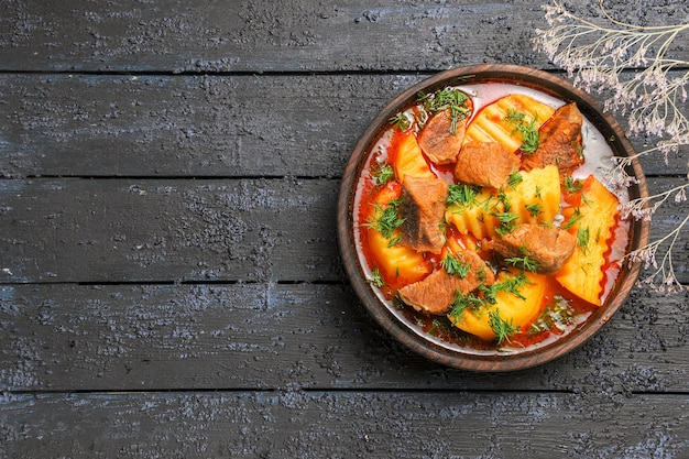 Widok z góry smaczna zupa mięsna z zieleniną i ziemniakami na ciemnym biurku