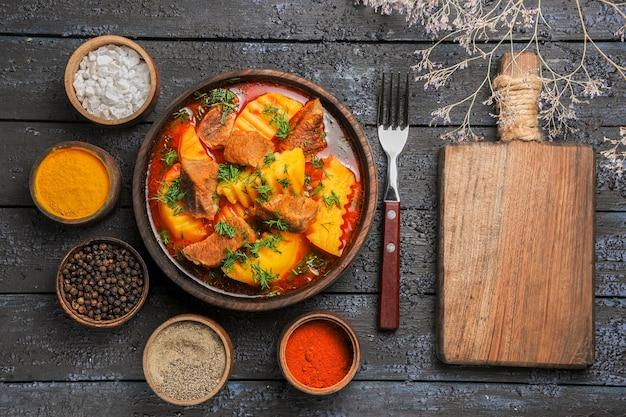 Widok z góry smaczna zupa mięsna z ziemniakami i przyprawami na ciemnym biurku