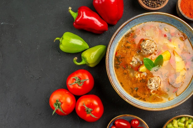 Widok z góry smaczna zupa mięsna ze świeżymi warzywami na ciemnym stole jedzenie danie zdjęcie posiłek