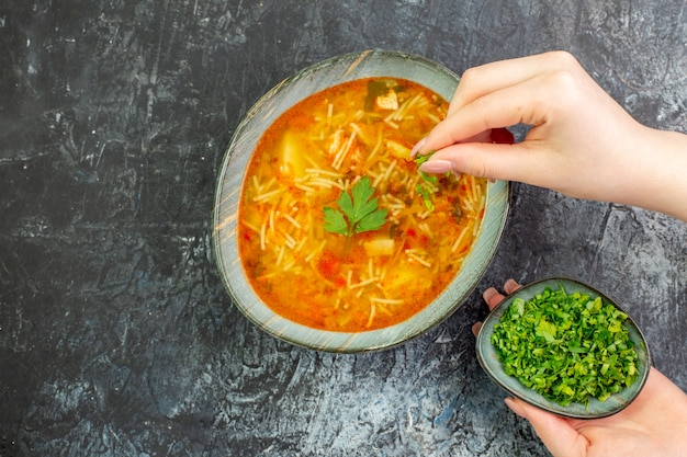 Widok z góry smaczna zupa wermiszelowa wewnątrz talerza z zieleniną na jasnoszarym stole