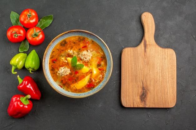 Widok z góry smaczna zupa z klopsikami z warzywami na ciemnym stole w kolorach potraw z sosem