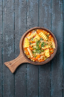 Widok z góry smaczna zupa z makaronu ze spiralnego włoskiego makaronu z zielenią na ciemnoniebieskim daniu kuchni na biurku włoska zupa z makaronem