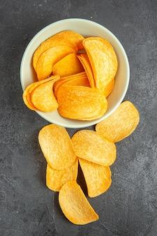 Widok z góry smaczne chipsy serowe wewnątrz płyty na ciemnym tle