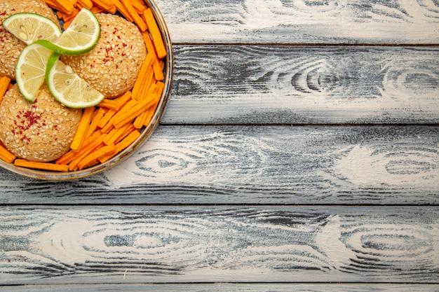 Widok z góry smaczne ciasteczka z plasterkami cytryny i sucharkami na rustykalnym szarym biurku ciasto biszkoptowo-cukrowe słodkie ciasteczka