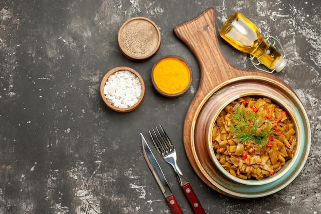 Widok z góry smaczne danie danie z zielonej fasoli na desce obok butelki oleju i trzech rodzajów przypraw na ciemnym stole