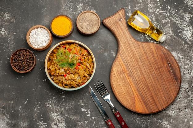 Widok z góry smaczne danie deska do krojenia obok talerz z zieloną fasolką widelec nóż butelka pomidorów oliwnych z szypułkami i cztery miski kolorowych przypraw na ciemnym stole