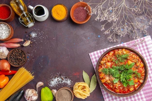 Widok z góry smaczne gotowane warzywa pokrojone w plasterki z sosem i przyprawami na ciemnym tle zupa z sosem jedzenie obiad posiłek
