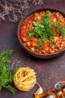 Widok z góry smaczne gotowane warzywa w plasterkach sos posiłek na ciemnej powierzchni posiłek zupa sos jedzenie danie obiadowe
