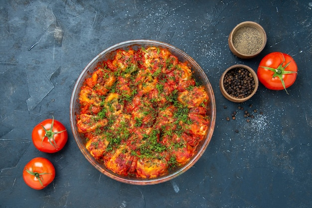 Widok z góry smaczne gotowane warzywa z mielonym mięsem i zieleniną wewnątrz patelni na niebieskim stole danie posiłek mięsna kuchnia rodzinna smak