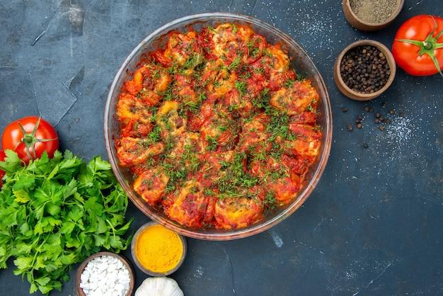 Widok z góry smaczne gotowane warzywa z przyprawami i zielenią na niebieskim stole danie posiłek mięso kuchnia jedzenie rodzinny smak
