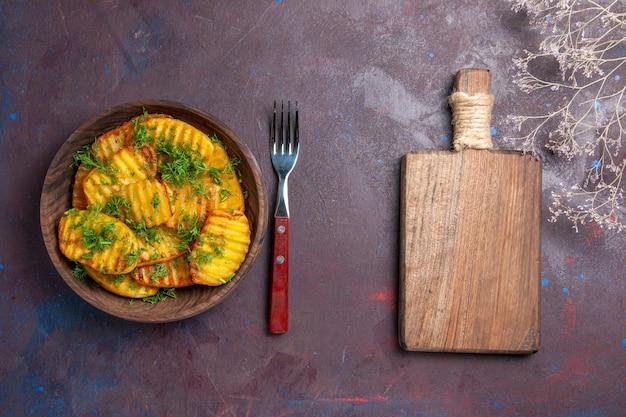 Widok z góry smaczne gotowane ziemniaki z zieleniną wewnątrz brązowego talerza na ciemnej powierzchni danie z mąką gotowanie cipek obiad ziemniak