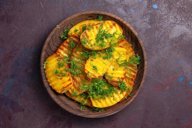 Widok z góry smaczne gotowane ziemniaki z zieleniną wewnątrz talerza na ciemnej powierzchni gotowanie chipsów ziemniaczanych na obiad
