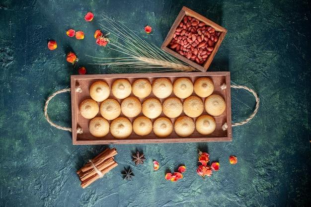Widok z góry smaczne herbatniki z orzeszkami ziemnymi na ciemnym tle cukrowe ciastko biszkoptowe ciasto orzechowe ciasto herbaciane kolor słodki