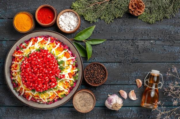 Widok z góry smaczne jedzenie apetyczne świąteczne jedzenie czosnek butelka oleju i sześć misek kolorowych przypraw obok świerkowych gałązek z szyszkami