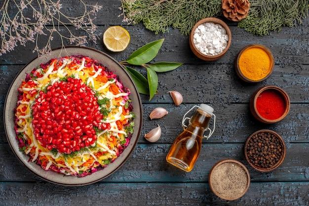 Widok z góry smaczne jedzenie smaczne danie świąteczne czosnek butelka oleju pięć misek kolorowych przypraw cytryna obok świerkowych gałązek z szyszkami