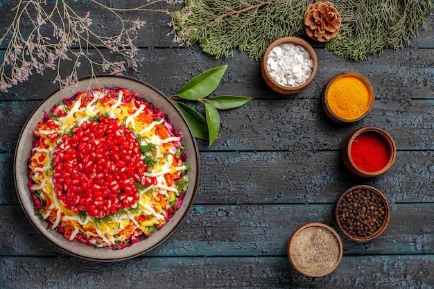Widok z góry smaczne jedzenie smaczne świąteczne jedzenie po lewej stronie i pięć misek kolorowych przypraw po prawej obok świerkowych gałązek z szyszkami
