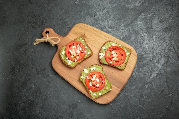 Widok z góry smaczne kanapki z awokado z pokrojonymi w plasterki czerwonymi pomidorami na szarym tle kanapka z burgerami chleba przekąska