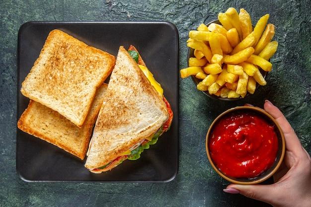 Widok z góry smaczne kanapki z szynką z tostami, frytkami i koncentratem pomidorowym na ciemnej powierzchni