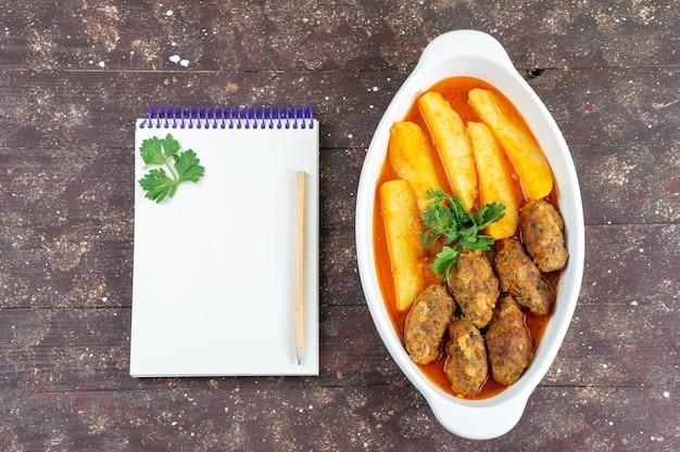 Widok z góry smaczne kotlety mięsne gotowane wraz z ziemniakami i sosem wewnątrz talerza z notatnikiem na brązowym biurku danie ziemniaczane danie mięsne obiad