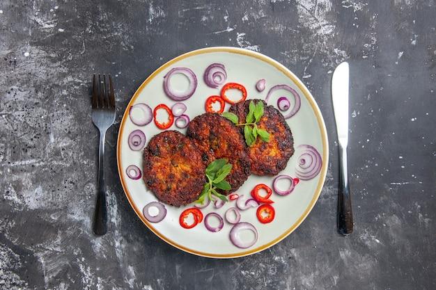 Widok z góry smaczne kotlety mięsne z krążkami cebuli na szarym tle zdjęcie kuchni posiłek