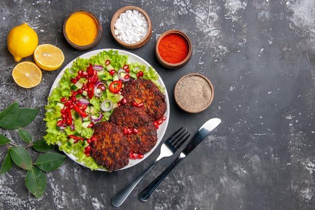 Widok z góry smaczne kotlety mięsne z sałatką i przyprawami na szarym tle zdjęcie danie posiłek posiłek