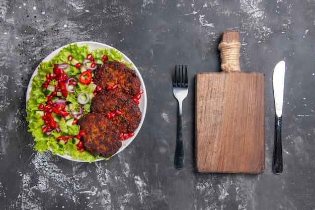Widok z góry smaczne kotlety mięsne ze świeżą sałatą na szarym biurku zdjęcie danie mięsne jedzenie