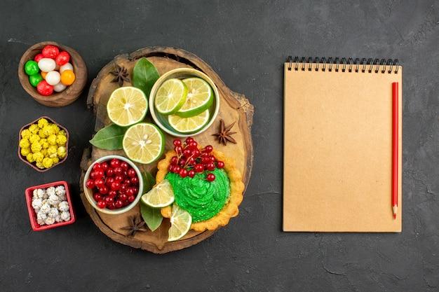 Widok z góry smaczne kremowe ciasto z cukierkami i owocami na ciemnym tle ciasteczka biszkoptowe słodkie