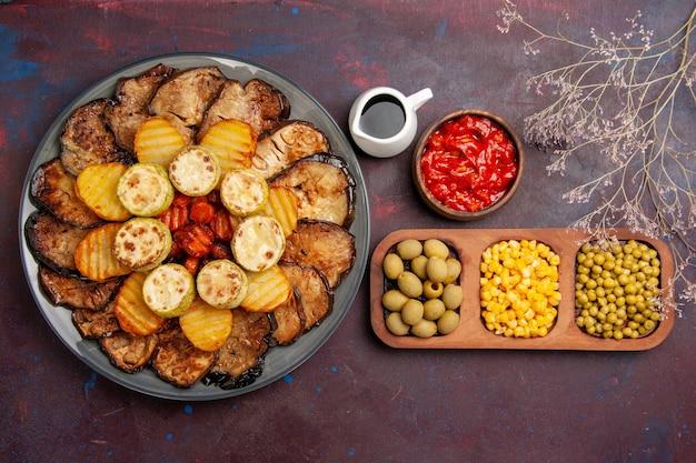 Widok z góry smaczne pieczone warzywa ziemniaki i bakłażany na ciemnym tle gotowanie w piekarniku posiłek piec warzywa