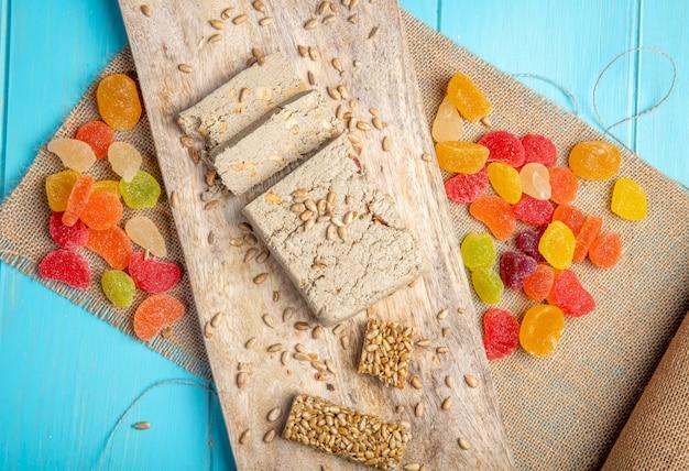 Widok z góry smaczne plastry chałwy słodkie kozinaki z nasion słonecznika i kolorowe cukierki marmoladowe na rustykalne