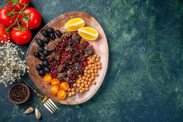 Widok z góry smaczne plastry mięsa smażone z fasolą, winogronami i plasterkami cytryny wewnątrz płyty, danie posiłek