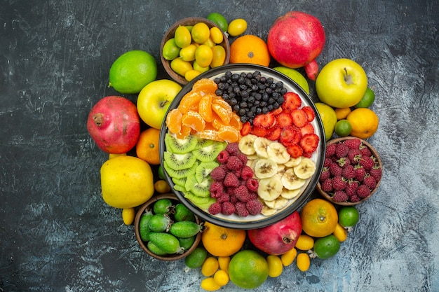 Widok z góry smaczne pokrojone owoce ze świeżymi warzywami na szarym tle