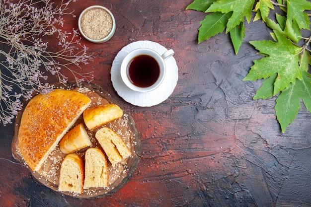 Widok z góry smaczne słodkie ciasto pokrojone w kawałki z filiżanką herbaty na ciemnej powierzchni