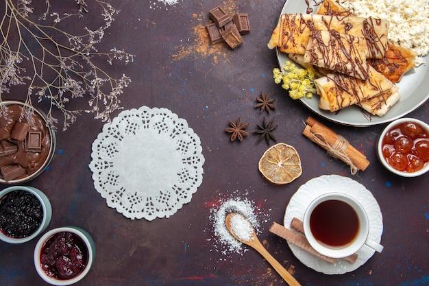 Widok z góry smaczne słodkie wypieki z filiżanką herbaty i dżemem na ciemnym biurku ciasto biszkoptowe cukier słodka herbata