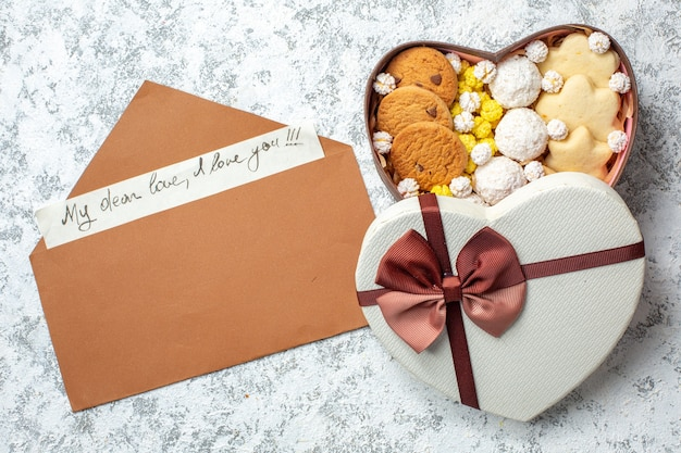 Widok z góry smaczne słodycze herbatniki ciasteczka i cukierki w pudełku w kształcie serca na białej powierzchni ciasto z cukrem herbata słodkie pyszne ciasto