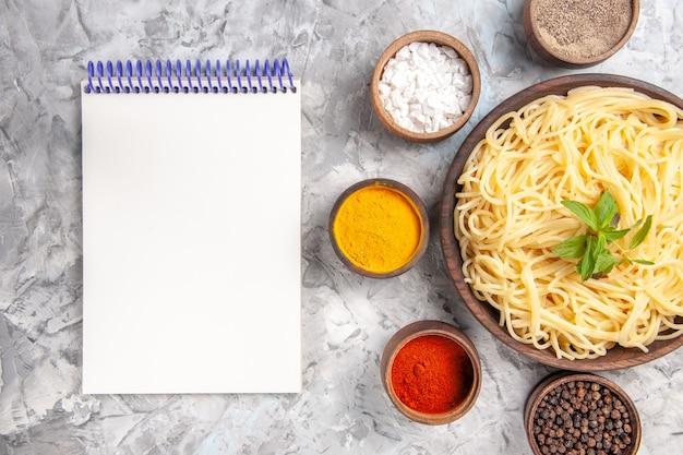 Widok z góry smaczne spaghetti z przyprawami na lekkim, białym cieście danie z makaronu
