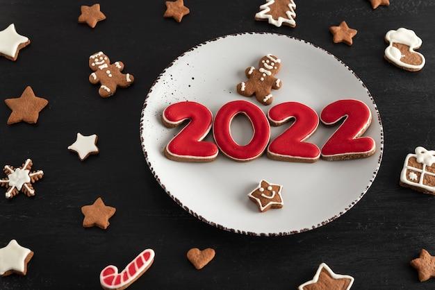 Widok z góry smaczne szkliwione malowane ciasteczka na białym talerzu: cyfry 2022, gwiazdki i jodła. koncepcja żywności nowy rok.