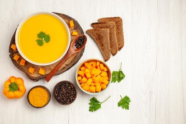 Widok z góry smacznego kremu z zupy dyniowej teksturowanej z ciemnymi bochenkami chleba na białym stole