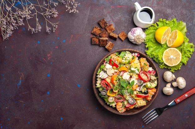 Widok z góry smacznej sałatki warzywnej ze świeżymi plasterkami cytryny na ciemnym