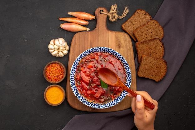 Widok z góry smaczny barszcz ukraiński zupa z buraków z ciemnymi bochenkami chleba na ciemnej podłodze posiłek warzywny obiad zupa spożywcza