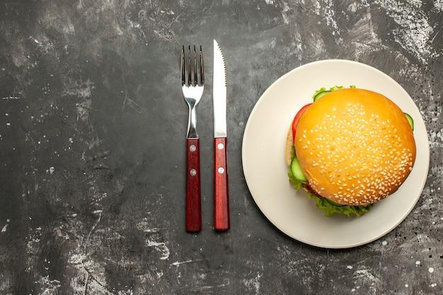 Widok z góry smaczny burger mięsny z warzywami na ciemnej powierzchni kanapka z bułką fast-food