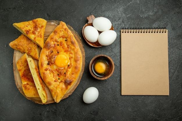 Widok z góry smaczny chleb jajeczny pieczony pokrojony w plasterki ze świeżymi jajkami na szarym tle chleb bułka ciasto śniadanie żywności