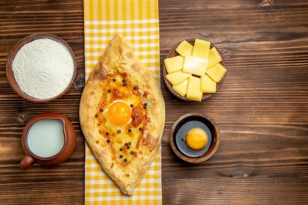 Widok z góry smaczny chleb jajeczny prosto z piekarnika z mlekiem i serem na drewnianym biurku posiłek chleb jajko bułka